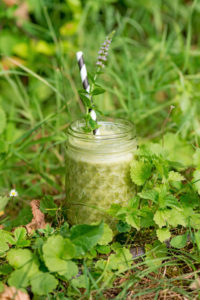 Glass with green smoothie, straw and mint blossom stands on overgrown ground