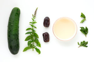 Ingredients for a wild herb smoothie as a laying picture on a pure white background.