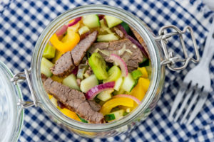 Close-up, mason jar with beef salad on blue and white checked cloth.