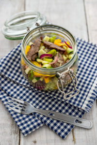 Beef salad, colorful vegetables, in a mason jar on a white wooden background and blue and white checked cloth, with a camping fork