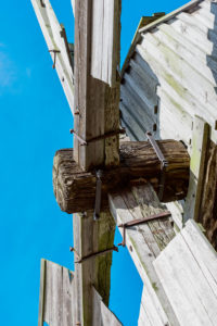 Detail of the rotating head of a post mill against a blue sky