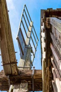 Flügelblatt einer Bockwindmühle vor blauem Himmel eingerahmt vom Mühlenbauwerk