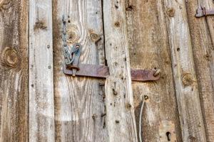 Mit einem verrosteten Eisenriegel verschlossene Holztür