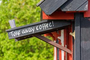 Kaffeebecher steht auf Vordach mit Take away coffee Schriftzug, Holzhaus im Anschnitt
