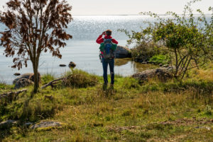 Mann mit Rucksack fotografiert aufs weite Meer hinaus.