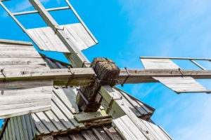 Detail des Drehkeuzes einer Bockwindmühle vor blauem Himmel