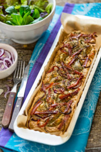 Foccacia fresh from the oven, in a rectangular tart pan, with green salad, extra red onions and artichokes