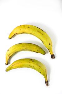 Drei Kochbananen auf weißem Untergrund