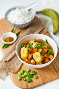 Asiatisches Curry mit Kochbanane und einer Schale weißem Reis auf Holzbrett mit Stäbchen und Deko