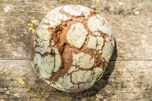 Runder, frisch gebackener Brotlaib von oben, Hintergrund verwittertes Holz