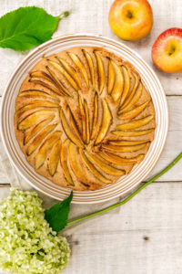 Apfelkuchen in runder Form gebacken und dekorativ mit Apfelspalten belegt, dekoriert mit zwei Äpfeln und einer weißen Hortensienblüte