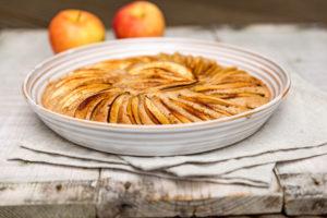 Apfelkuchen in runder Form gebacken und dekorativ mit Apfelspalten belegt, dekoriert mit zwei Äpfeln