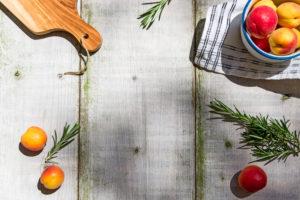 Mit Aprikosen und Rosmarin verzierter Gartentisch, mit mittigem Textfreiraum