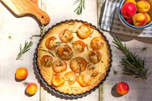 Aprikosen-Schmand-Tarte auf Gartentisch mit Aprikosen Rosmarin Verzierung, Schale mit Aprikosen und Schneidebrett angeschnitten am Bildrand.