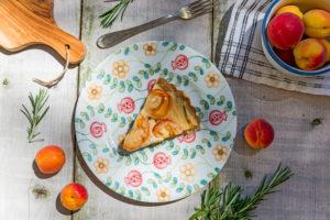 Ein Stück Aprikosenkuchen auf buntem Teller Umrahmt von Aprikosen, Rosmarin, Gabel, und Schneidebrett