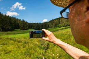 Mann fotografiert Landschaft mit dem Smartphone, auf dem Display ist die Landschaft zu sehen, Bild im Bild
