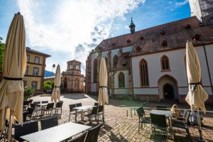 Morgens auf dem Platz vor der Stiftskirche, im Vordergrund Tische und Stühle von einem Restaurant.