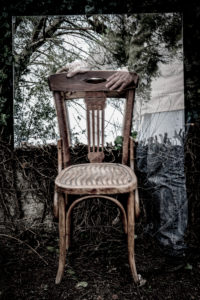Poetic image of reflections in a garden and forest with a wooden chair in an atmosphere of a dream