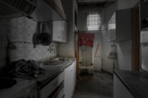 Interior of an apartment with abandoned walls, ceilings and floors in the center of a European city interior kitchen without people and with a dark atmosphere