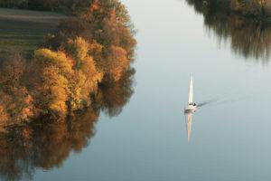 Segelboot segelt auf dem Fluss Neckar im Herbst, Deutschland, Baden-Württemberg
