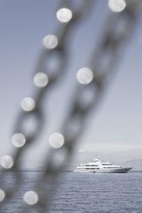 Blick vom Schiff auf das Mittelmeer mit Takelage im Vordergrund zu einer Yacht