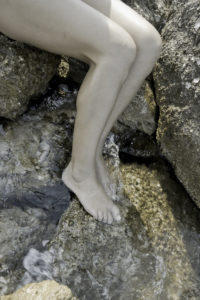 Naked legs of a girl, shore