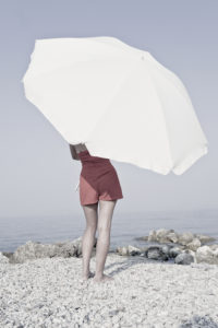 Corfu, girl on the beach with beach umbrella