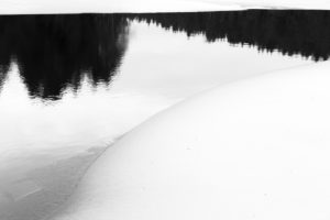 Sweden, winter, reflexion in the water with ice, snow and trees