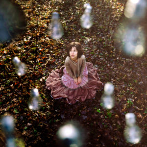 Woman with serious expression sitting on forest floor,surrounded by light bulbs -drops