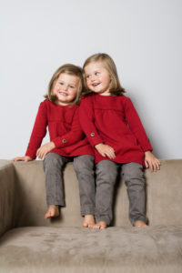 Twins, girls sitting on sofa