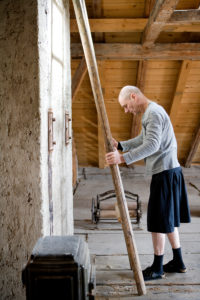 Man in skirt with ladder on an attic