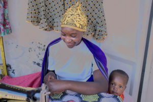 African woman with her baby on the sewing machine