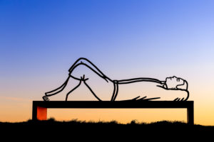 Lying man on a bench at sunset