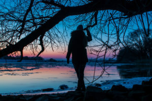 Silhouette of a Woman standing at a beach. Twilight evening mood at the frozen river Elbe in Geesthacht near Hamburg
