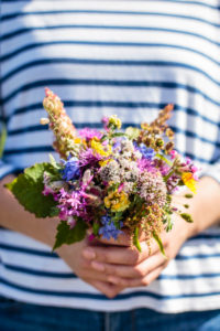 A young woman is holding a bouquet of freshly picked wildflowers, Europe, Denmark, Bornholm,