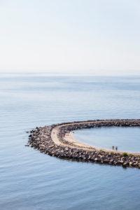 Bathers at the pier of Vang, former port of debarkation of the granite quarry, Europe, Denmark, Bornholm,