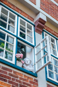 Europe, Germany, Lower Saxony, Otterndorf. Bust and roses in an open window of the former Latin school (1614).
