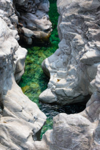 Europe, Switzerland, Ticino, Vallemaggia. The bed of the Maggia, cut deep into the rock and glowing in the sun.