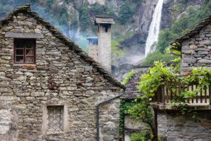 Europe, Switzerland, Ticino, Foroglio. View through the picturesque old village of Foroglio to the Calnègia waterfall.