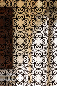 Europe, Italy, Piedmont, Orta San Giulio. An ornate, wrought-iron gate leads into the atrium of a house in the old town.