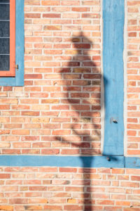 Europe, Germany, Lower Saxony, Otterndorf. In the morning sun, the shadow of an old street lamp falls onto the bare red brick wall of the teahouse.