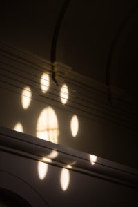 Europe, Germany, Lower Saxony, Delmenhorst. Through the window rose, inspired by churches, sunlight shines into the hall of the turbine house of the Norddeutsche Wollkämmerei and Kammgarnspinnerei (Nordwolle).