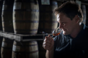 Saint James, rum barrels maturing in wooden barrels, production manager Marc Sassier tasting from old barrels