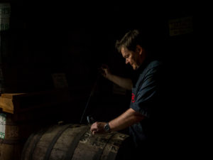 Saint James, rum maturing in wooden barrels, production manager Marc Sassier tasting from old barrels