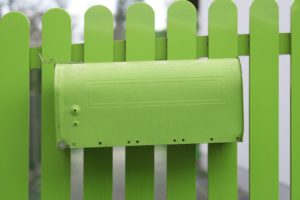 Green mailbox at pale green fence,