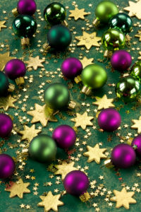 Green and purple Christmas balls, scattering stars,