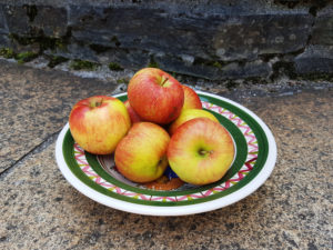 A plate of apples on stone floor