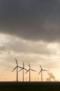 Germany, Lower Saxony, East Friesland, Krummhörn, wind power plants close Groothusen, in the background Dutch industrial plants,