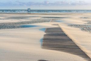 Deutschland, Niedersachsen, Ostfriesland, Juist, am Strand bei Sturm mit Sandverwehungen.
