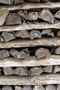 Firewood warehouse with gray logs.